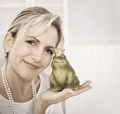 stock photo of hand kiss  - Single attractive maturer woman kissing a frog king in her hands - JPG