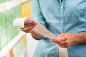 picture of receipt  - Unrecognizable woman in light blue shirt checking a long grocery receipt at store - JPG