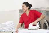 image of laundromat  - Happy young female employee ironing while looking away in Laundromat - JPG
