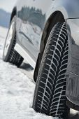 foto of four-wheel drive  - Car with winter tyres installed on light alloy wheels in snowy outdoors road - JPG