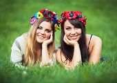 stock photo of national costume  - Two beautiful laughing girl in Ukrainian national costumes lie on the green grass - JPG