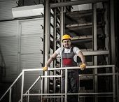 pic of heavy equipment operator  - Man in a safety hat on a factory   - JPG