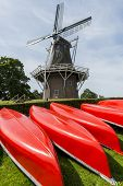 foto of stelles  - Several red canoes with in the background a great Dutch mill in Garnwerd - JPG
