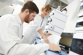 stock photo of chemistry technician  - researchers team work at computer scientific analysing data out scientific test in chemistry laboratory - JPG