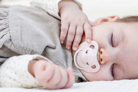 foto of pacifier  - Cute baby girl with pacifier sleeping over white bedcover - JPG