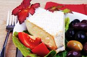picture of brie cheese  - aged brie cheese on salad in white dish over red cloth on with olives and tomato over wooden table - JPG
