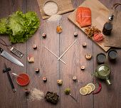 stock photo of sushi  - Sushi time in the form of a wall clock on a wooden background - JPG