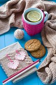 picture of blanket snow  - A cup of tea in sweater with lemon old notebook with hearts of felt beige knitted blanket and spokes lie on blue background - JPG