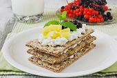 foto of mango  - rye bread with cottage cheese mango and berries of mountain ash on a white wooden background - JPG