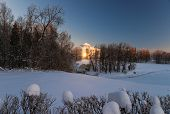 stock photo of winter palace  - Pavlovsky palace witn glaring sunlight reflection at window in winter day and beautiful snow covered parc Pavlovsk Russia - JPG
