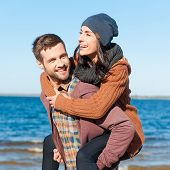 pic of heterosexual couple  - Beautiful young loving couple having fun while walking by the beach - JPG