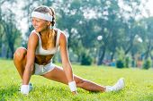 image of legs air  - Young fitness girl stretching in park on green grass