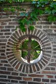 foto of ivy  - The stone wall catches the attention with a small round window grill - JPG