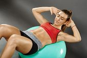 stock photo of crunch  - Young fit woman doing abs crunches on gym ball - JPG