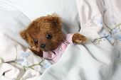 image of pyjama  - Cute teddy bear in pink pyjama resting in the bed - JPG