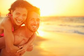 stock photo of hug  - Lovers couple in love having fun dating on beach portrait - JPG