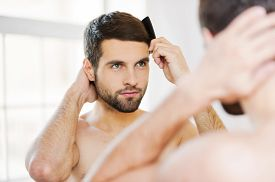 picture of hair comb  - Rear view of handsome young beard man combing his hair while standing against a mirror - JPG