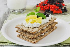 image of mountain-ash  - rye bread with cottage cheese mango and berries of mountain ash on a white wooden background - JPG