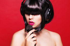 picture of karaoke  - Woman listening to music on headphones enjoying a singing - JPG