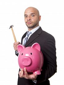 image of spanish money  - bald Hispanic businessman with hammer in his hand holding pink piggybank ready to break the piggy bank and take money and savings out isolated on white background - JPG