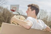 pic of early 20s  - Young man resting after exhausting basketball game - JPG