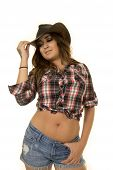 picture of cowgirl  - a cowgirl in her plaid top holding on to the brim of her hat - JPG