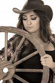 pic of cowgirls  - a cowgirl looking down at a wagon wheel with tattoos on her body - JPG