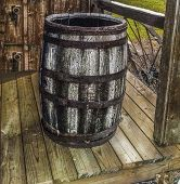 stock photo of shacks  - Old wooden rain barrel sitting on a wooden porch and shack  - JPG