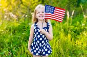 picture of waving  - Funny little girl with long curly blond hair holding an american flag waving it and laughing on sunny day in summer park - JPG