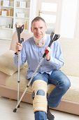 image of crutch  - Man with leg in neck brace - JPG