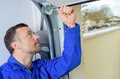 picture of garage  - Man installing a garage door - JPG