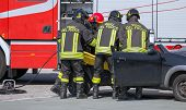 stock photo of firehouse  - brave Firefighters pull in wounded by car plates after highway crash - JPG