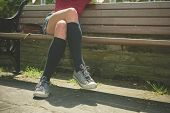 pic of knee-high socks  - A young woman wearing knee high socks is sitting on a park bench - JPG