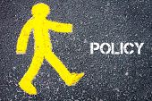 pic of pedestrians  - Yellow pedestrian figure on the road walking towards POLICY - JPG