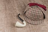 picture of private investigator  - Deerstalker or Sherlock Hat and Tobacco pipe on Old Wooden table - JPG