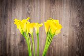 stock photo of calla  - Bunch of callas in the vase on wooden background - JPG