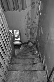 foto of abandoned house  - Crooked wooden staircase and peeling paint wall in abandoned house - JPG