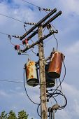 stock photo of transformer  - Old wood power pole with rusty transformers wires insulators fuses and entrance heads - JPG