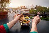image of indian food  - Woman eating traditional Indian food in rooftop restaurant with Taj Mahal view in Agra Uttar Pradesh India - JPG