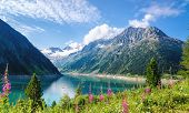 stock photo of crystal clear  - Crystal clear alpine lake Schlegeis with colorful flowers and mountain peaks in background - JPG
