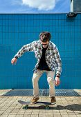 pic of skateboard  - Skateboarder jumping in city on skateboard at the background wall tiles - JPG