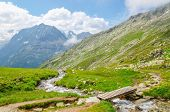 stock photo of mountain-high  - Beautiful alpine landscape with a mountain brook on the background of the high peaks of the mountains - JPG