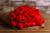 stock photo of sackcloth  - Bouquet of red tulips wrapped in sackcloth on wooden background - JPG