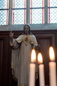 image of sacred heart jesus  - Statue of Jesus Christ in Church with Lit Burning Candles in Foreground - JPG