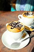 stock photo of clefs  - Cups of cappuccino with treble clef on foam on table in cafe - JPG
