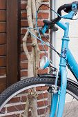 stock photo of lent  - Light Blue Bicycle lent against Brick Wall - JPG