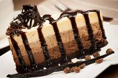 stock photo of vanilla  - chocolate vanilla cake with chocolate sauce on white plate decorated with vanilla stick and coffee beans - JPG
