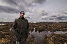 stock photo of marshlands  - Man traveler on marshland against the backdrop of rain clouds - JPG