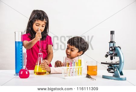 Постер, плакат: 4 year old indian boy and girl doing science experiment science Education asian kids and science e, холст на подрамнике