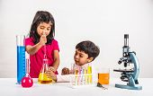 Постер, плакат: 4 year old indian boy and girl doing science experiment science Education asian kids and science e
